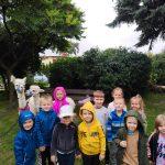 Grupa dzieci pozująca do zdjęcia w ogrodzie przedszkolnym. Za dziećmi stoją dwie alpaki.