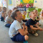 Siedmioro dzieci siedzących w sali przedszkolnej na dywanie.