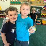 Dwóch chłopców stojących obok siebie w sali przedszkolnej i obejmujących się. W tle widać dziewczynkę i tyłem stojącego chłopca.