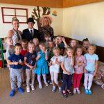 Grupa dzieci stojąca w sali przedszkolnej, trzymająca w rękach lizaki. Za dziećmi stoją trzy Panie.ę