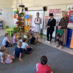 Grupa dzieci siedząca na dywanie w sali przedszkolnej. Naprzeciwko dzieci stoją trzy Panie.