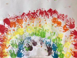 Tęcza odbita z rączek pomalowanych farbami