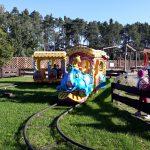 Kolejka z lokomotywą w kształcie słonia, jedzie po torach. Po prawej stronie przy płotku, stoi troje dzieci i obserwuje jadącą kolejkę.
