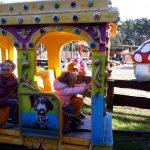 Czworo dzieci siedzi w kolorowym wagoniku kolejki.