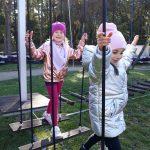 Dwie dziewczynki przechodzą przez linowy tor przeszkód.