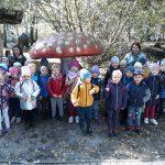 Grupa dzieci z trzema paniami pozują do zdjęcia pod figurą muchomora.