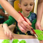 Chłopiec siedzi przy stole ma pomalowane dłonie na zielono, które odciska na kartce papieru.