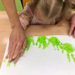 Dziewczynka siedzi przy stole ma pomalowane dłonie na zielono, które odciska na kartce papieru.