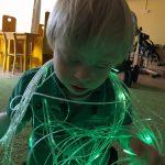 Chłopiec siedzi na dywanie, na sobie na wiązki światłowodów.