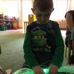 Chłopiec siedzi na dywanie. W rękach trzyma światłowody.
