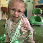 Dziewczynka siedzi na dywanie, na sobie na wiązki światłowodów.