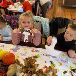 Troje dzieci siedząctych obok siebie przy stole i trzymajacych grzybki z papieru.