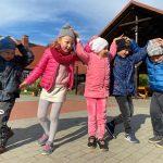 Pięcioro dzieci stojących obok siebie i trzymających ręce na głowie.