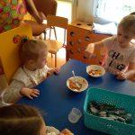 Dwie dziewczynki jedzą przygotowaną sałatkę owocową.