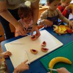 Dzieci przy stoliku kroją owoce. Jedna dziewczynka z pomocą nauczyciela.