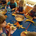 Kilkoro dzieci siedzi przy stoliku , krojąc przygotowane owoce.
