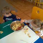 Dwoje dzieci siedzi przy stoliku. Dziewczynka wrzuca pokrojone owoce do miski.