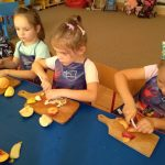 czworo dzieci siedzi przy stoliku i kroi nożem owoce na deseczce