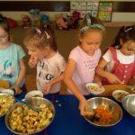 Czworo dzieci z stoi przy stoliku i nakładają owoce z misek ustawionych na stole.