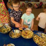Troje dzieci z nauczycielem stoi przy stoliku i nakładają owoce z misek ustawionych na stole.