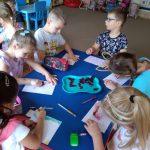 Sześcioro dzieci siedzi przy stoliku i rysują. na środku stołu jest taca z kawałkami czerwonej kapusty.ą
