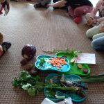 Dzieci siedzą w kole na dywanie, przed nimi tace z warzywami.
