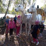 Cztery dziewczynki stoją przy figurze białych koni z karocą.