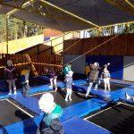 Dzieci skaczą na trampolinach.
