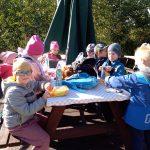 Dzieci siedzą na drewnianych ławkach przy stole i spożywają posiłek. Stół przykryty jest jasną ceratą w kratkę.
