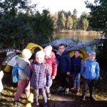 Trzy dziewczynki i pięcioro chłopców stoi przed dużym owadem. W tle widać staw.