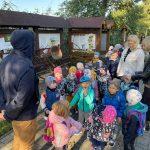 Dzieci i nauczycielki stoją na ścieżce obok wystawionego eksponatu i słuchają przewodnika.