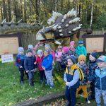 Grupa dzieci pozuje do zdjęcia przy figurze dinozaura. Widoczne są również tablice informacyjne o znajdujących się tam dinozaurach.
