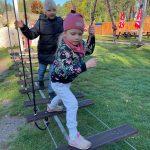 Chłopiec i dziewczynka przechodzą przez linowy tor przeszkód. Dziewczynka jako pierwsza. Ma ubraną kurtę w kwiaty oraz różową chustkę i czapkę.