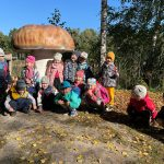 Grupa dzieci stoi pod ogromnym grzybem. Dzieci w pierwszym rzędzie kucają.
