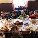 Siedmioro dzieci siedzących przy stole i zjadajacych słodkości.