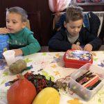 Dwóch chłopców siedzących przy stole i zjadających słodkości.