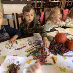 Czworo dzieci siedzących przy stole i kolorujących kolorowanki.