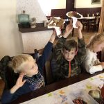 Czworo dzieci siedzących obok siebie przy stole. Dwóch chłopców trzyma ręce do góry z papierowymi grzybkami. Jedna dziewczynka koloruje papierowego grzybka