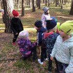 Ośmioro dzieci będących w lesie. Chopiec i dziewczynka glaszczą psa.