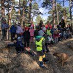 Grupa dzieci i pięć pań pozujących do zdjęcia w lesie. Przed dziećmi siedzi pies.