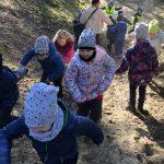 Grupa dzieci biegających w lesie. Z tyłu idzie Pani, która trzyma dwoje dzieci za ręce.