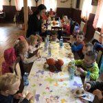 Grupa dzieci siedzaca przy trzech stołach i zjadająca ziemniaki z gzikiem. Przy pierwszym stle stoi kobieta.