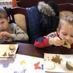 Dwóch chłopców siedzących przy stole i jedzących ziemniaki z gzikiem.