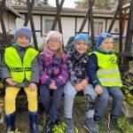 Czworo dzieci siedzących obok siebie na ławce w ogrodzie.