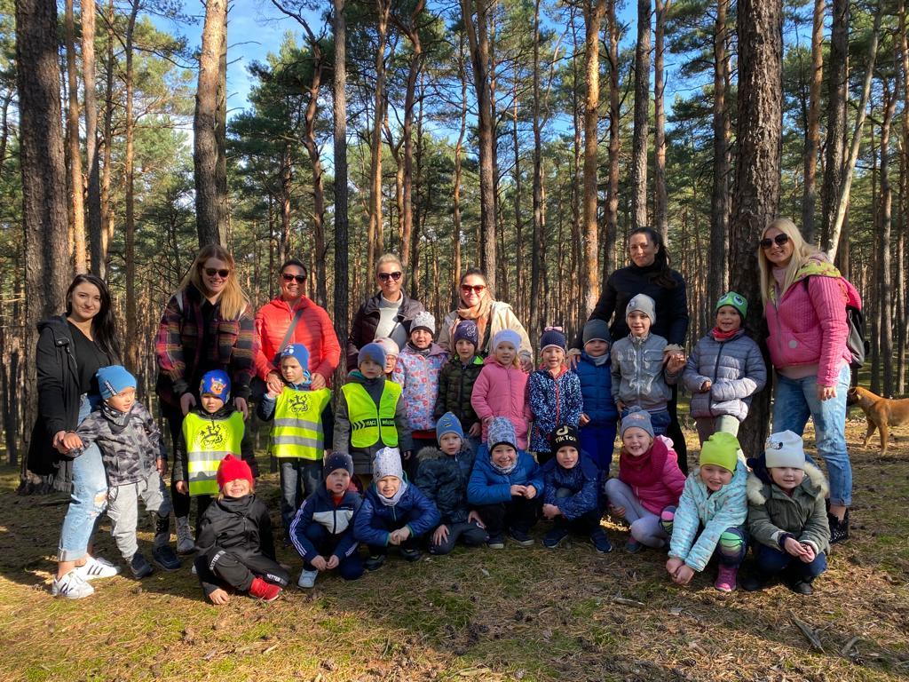 Grupa dzieci pozujaca do zdjęcia w lesie w dwóch rzędach. W trzecim rzędzie stoi siedem pań.